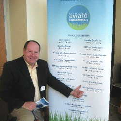 Man in front of the CoolCalifornia small business award winners banner.